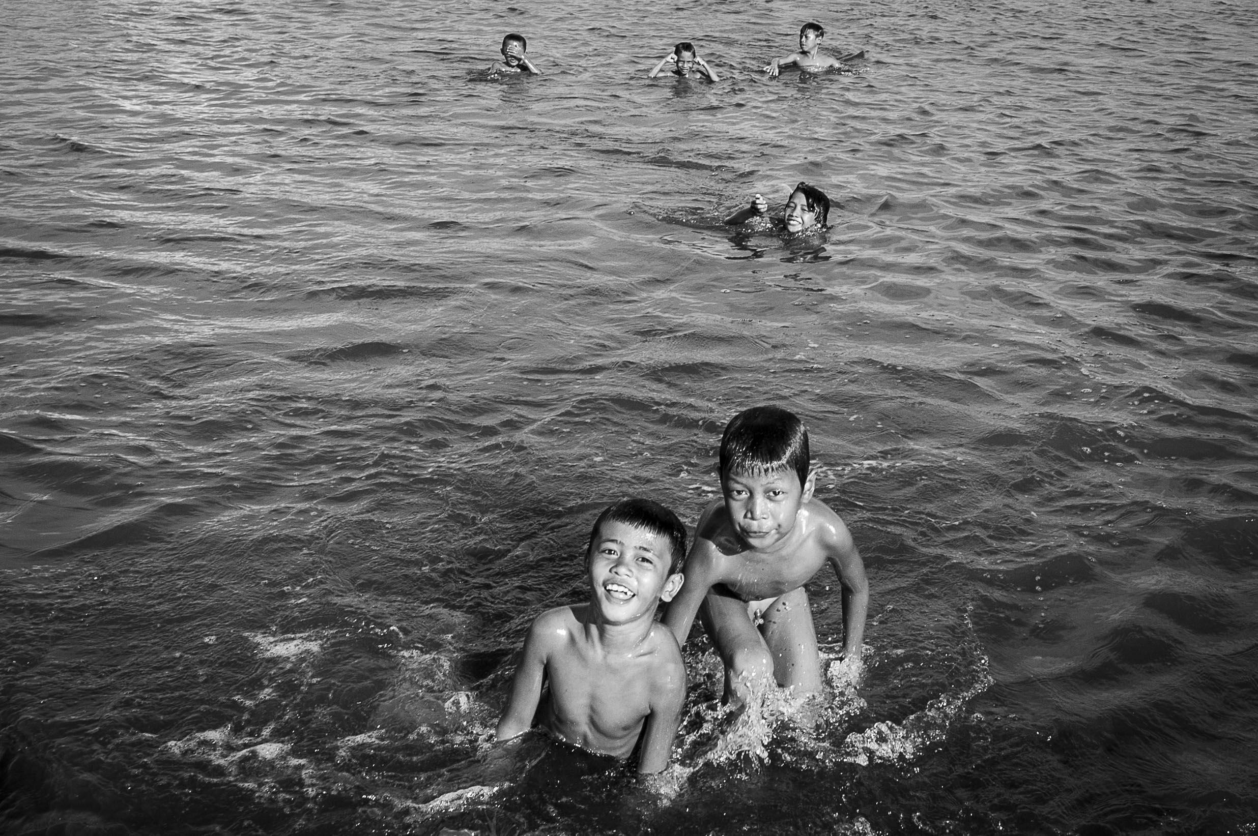 Spelende kinderen in het water van Davao